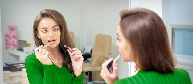 Красивая молодая кавказская женщина, наносящая блеск на губы, глядя в зеркало