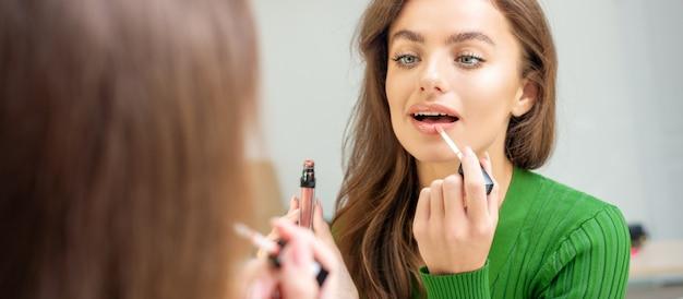 鏡を見ている唇に光沢を適用する美しい若い白人女性