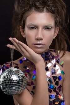 Beautiful young caucasian woman holding disco ball