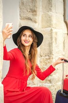 Красивая молодая кавказская женщина в черной шляпе, глядя на смартфон, улыбаясь и сидя на лестнице у двери на открытом воздухе.