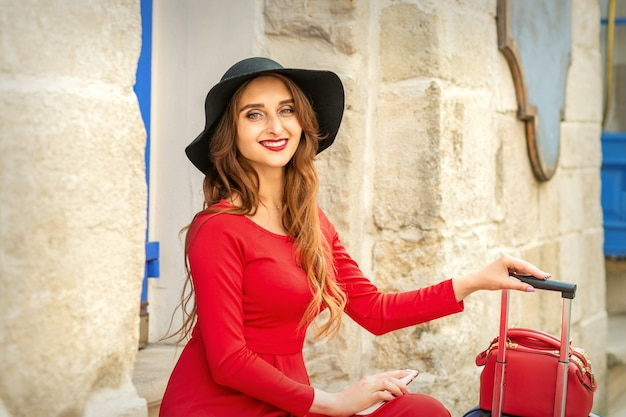 笑顔と屋外のドアの階段に座っている黒い帽子の美しい若い白人女性