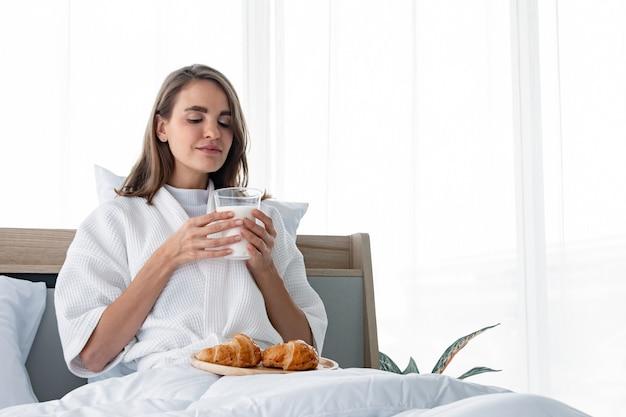 朝食を食べる準備ができているパジャマの美しい若い白人女性は朝の牛乳とクロワッサンです