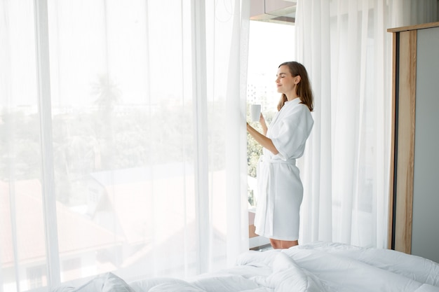 잠에서 깨어난 후 집에 있는 침실 창가에서 마실 준비가 된 흰색 커피 한 잔을 들고 잠옷을 입은 아름다운 백인 여성. 창가에 서서 커피를 마시는 여자.