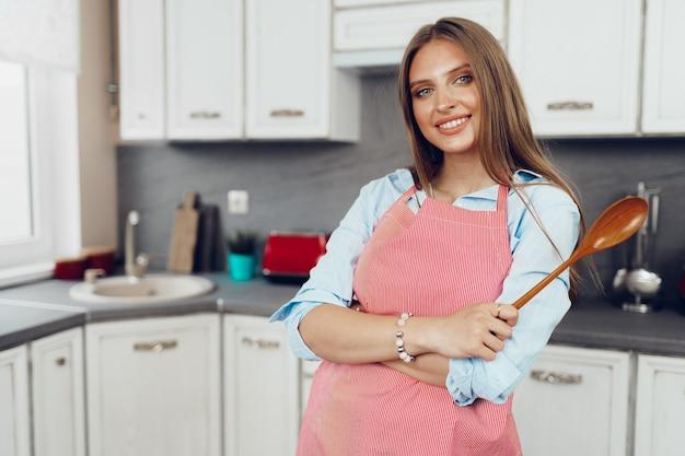 Красивая молодая кавказская женщина в красном фартуке, стоя с деревянной ложкой на кухне
