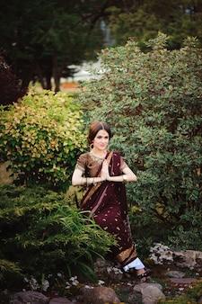 Красивая молодая кавказская женщина в традиционном индийском сари одежды с свадебным макияжем и украшениями и татуировкой хной на руках.