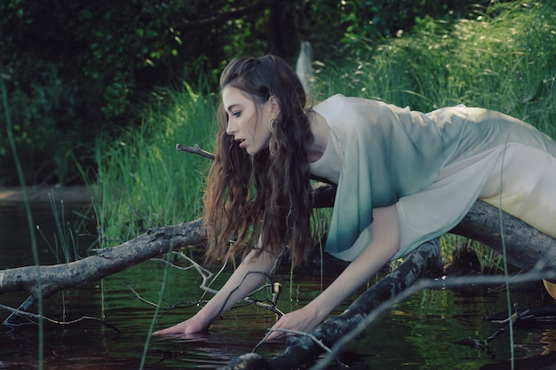 Beautiful young caucasian woman leaning on the tree branch over the river trying to reach the water.