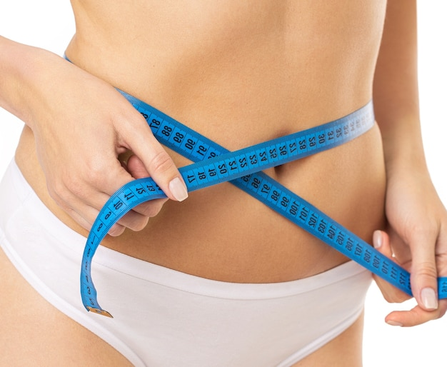 Beautiful young caucasian woman measuring her figure size with tape measure. womans holding centimeter and measuring the size of thin body.