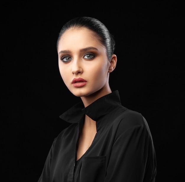 Beautiful young caucasian woman portrait on black wall