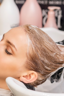 Beautiful young caucasian woman receiving wash her hair in a hair salon