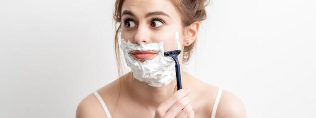 아름 다운 젊은 백인 여자 흰색 배경에 면도기로 그녀의 얼굴을 면도. 그녀의 얼굴에 면도 거품을 가진 예쁜 여자