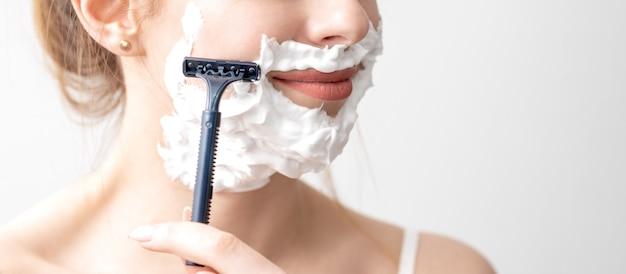 白い壁にかみそりで顔を剃っている美しい若い白人女性。彼女の顔にシェービングフォームを持つきれいな女性