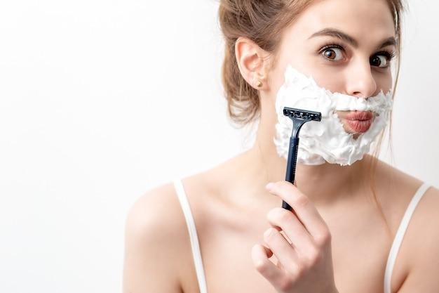 Красивая молодая кавказская женщина бреет лицо бритвой. красивая женщина с пеной для бритья на лице