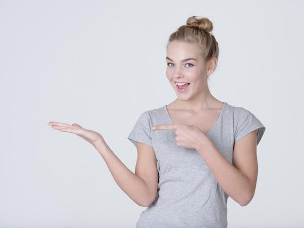 La bella giovane donna caucasica mostra la mano del palmo isolato su priorità bassa bianca