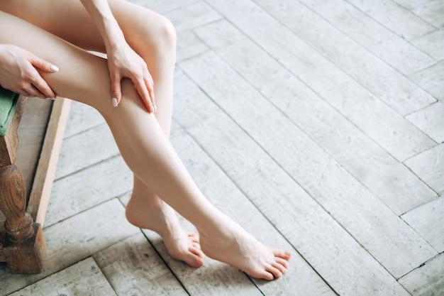 Красивая молодая женщина кавказской показывая ее ноги, конец вверх.