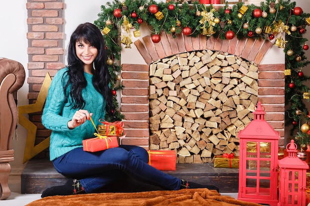 Beautiful young caucasian woman sitting near a decorative fireplace in a christmas interior.