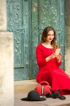 Красивая молодая кавказская женщина, сидящая на лестнице у двери с чемоданом и смартфоном путешествия, носящим длинное красное платье.