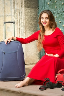 Beautiful young caucasian woman sitting on the stairs by the door wearing black hat and long red dress with travel suitcase and smartphone