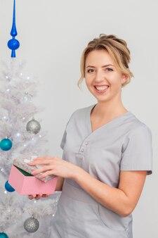 クリスマスツリーの近くのギフトボックスと医療の制服に笑みを浮かべて美しい若い白人女性