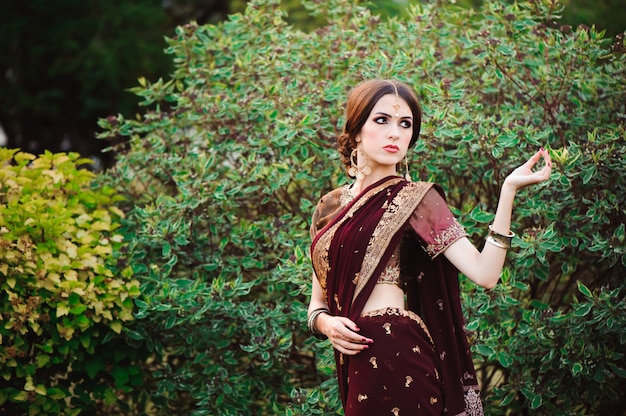 Beautiful young caucasian woman in traditional indian clothing sari with bridal makeup and jewelry and henna tattoo on hands.
