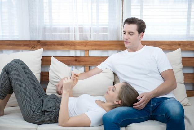 スマート携帯電話を使用して美しい若い白人女性は、自宅のリビングルームのソファーに座る男の膝の上にあります。