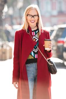 コーヒーを飲みながら野外を歩いている美しい若い白人女性。