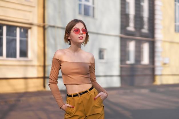 美しい若い白人女性は街の暖かい夏の晴れた日の通りを歩く
