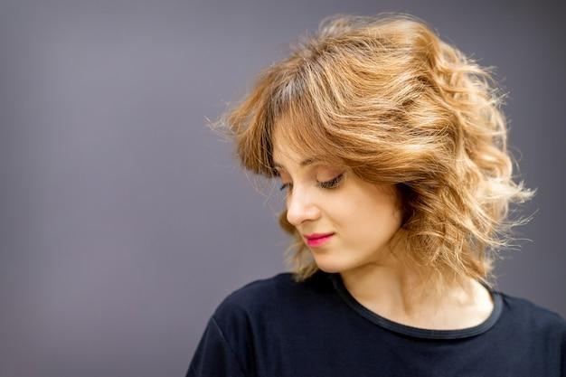 Красивая молодая кавказская женщина с красной короткой вьющейся прической смотрит вниз на темном фоне