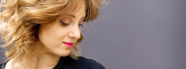 Красивая молодая кавказская женщина с красной короткой вьющейся прической, смотрящей вниз на темном фоне.