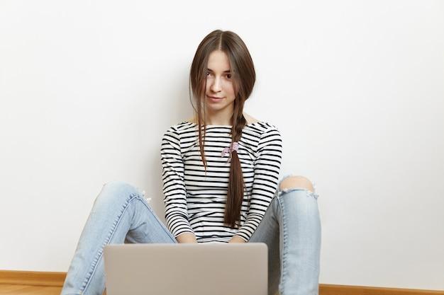 一般的なラップトップを使用して乱雑な髪型と美しい若い白人女性