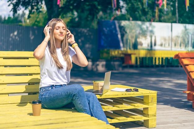 Красивая молодая кавказская женщина с волнистыми светлыми волосами в повседневной одежде, наслаждаясь музыкой на улице
