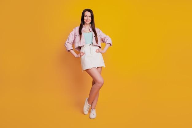 Красивая молодая очаровательная женщина позирует на желтом фоне.