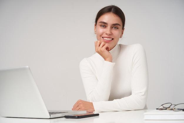 ポニーテールの髪型で美しい若い陽気な黒髪の女性は、上げられた手で彼女のあごをもたれ、魅力的な笑顔でカメラを見て、白い壁の上でポーズをとって幸せに見ています