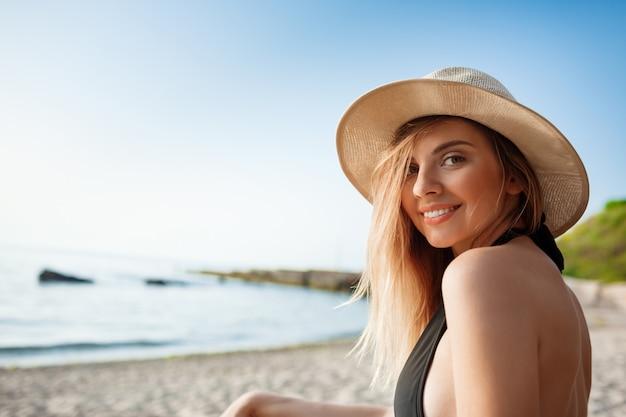 La bella giovane ragazza allegra in cappello riposa alla spiaggia di mattina