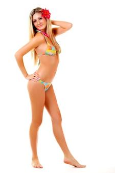 Красивая молодая жизнерадостная девушка в купальнике с красным цветком в волосах