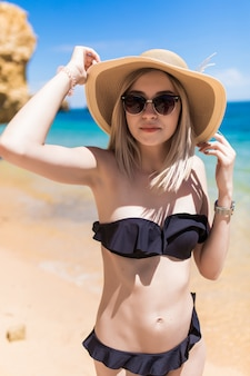 帽子とサングラスの美しい若い陽気な女の子は海の近くの朝のビーチで休む