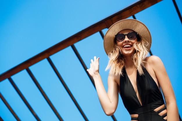 Красивая молодая жизнерадостная девушка в шляпе и солнцезащитные очки лежит на утреннем пляже