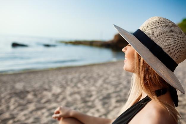 Красивая молодая жизнерадостная девушка в шляпе лежит на утреннем пляже