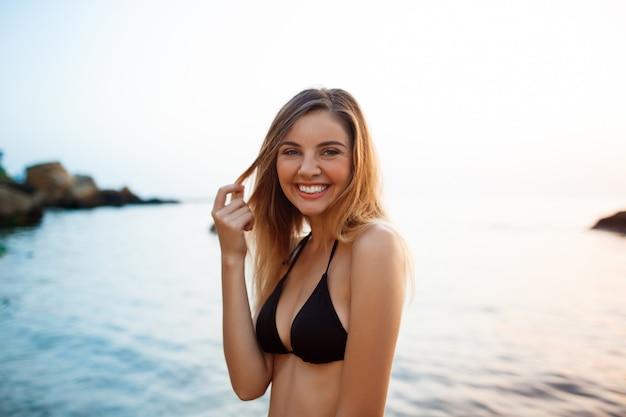 Красивая молодая жизнерадостная девушка отдыхает на утреннем пляже