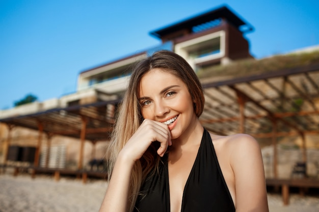 Beautiful young cheerful girl rests at morning beach