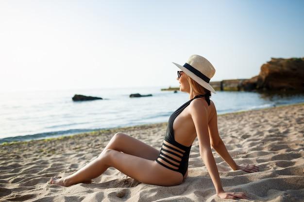 Красивая молодая жизнерадостная девушка в очках и шляпе отдыхает на пляже утром