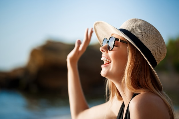 Beautiful young  cheerful girl wearing glasses and hat rests at morning beach