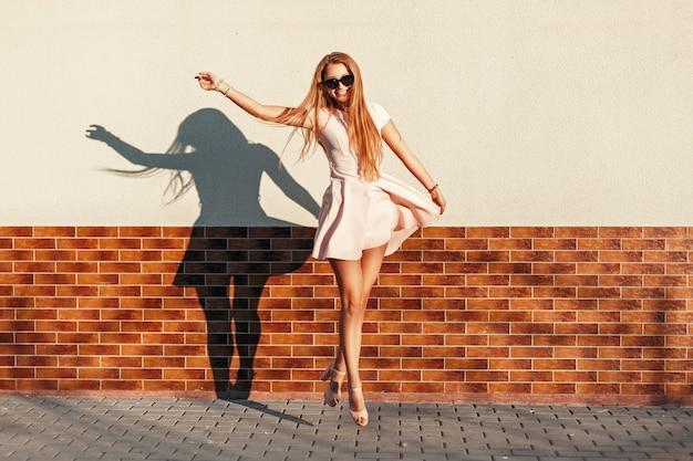 Красивая молодая веселая девушка с улыбкой прыгает у стены. радоваться, веселиться