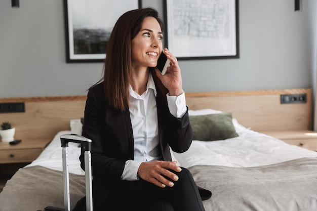 Beautiful young cheerful happy business woman in formal wear clothes indoors at home with suitcase talking by mobile phone.