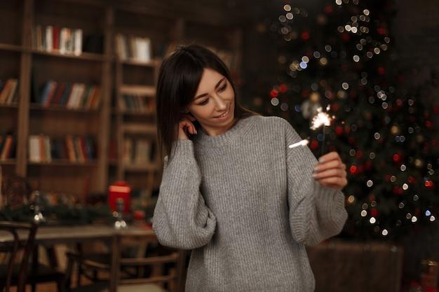 ニットのファッショナブルなセーターを着た美しい若い陽気な女性は、ヴィンテージの部屋でクリスマスツリーの線香花火を保持しています。魔法の新年の雰囲気。かわいい女の子。