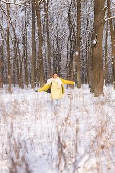 雪景色の冬の森の美しい若い陽気な女性は、冬に喜び、暖かい服を着て雪を楽しんでいます