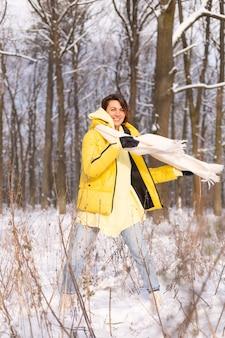재미 눈 덮인 풍경 겨울 숲에서 아름 다운 젊은 쾌활 한 여자는 따뜻한 옷에 겨울과 눈에 기뻐