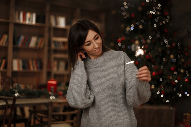 Beautiful young cheerful woman in a knitted fashionable sweater is holding a sparkler of the christmas tree in a vintage room. magic new year's atmosphere. cute girl.
