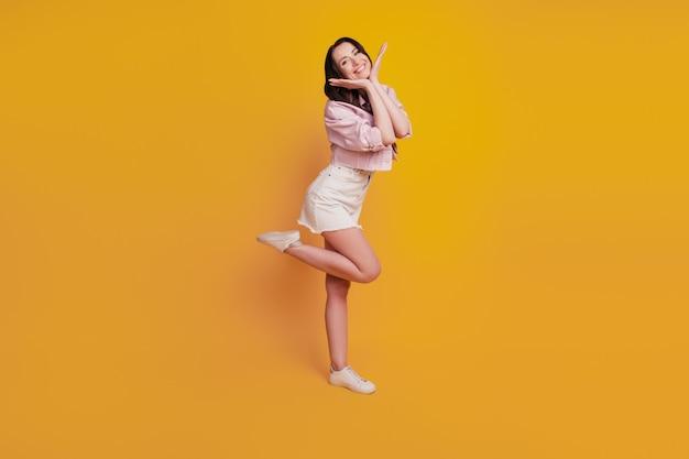 Красивая молодая жизнерадостная женщина позирует на желтом фоне.