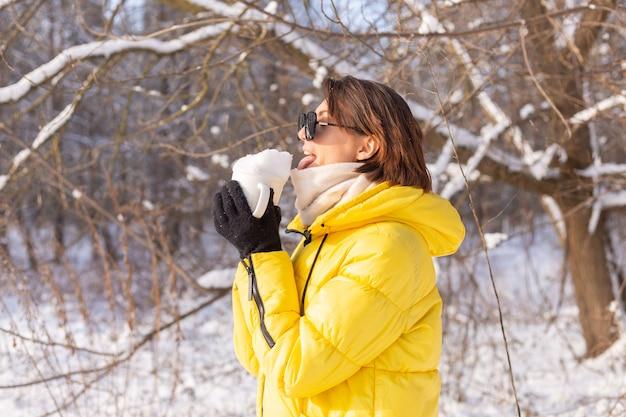 Bella giovane donna allegra in una foresta di inverno paesaggio innevato in occhiali da sole con una tazza piena di neve divertendosi