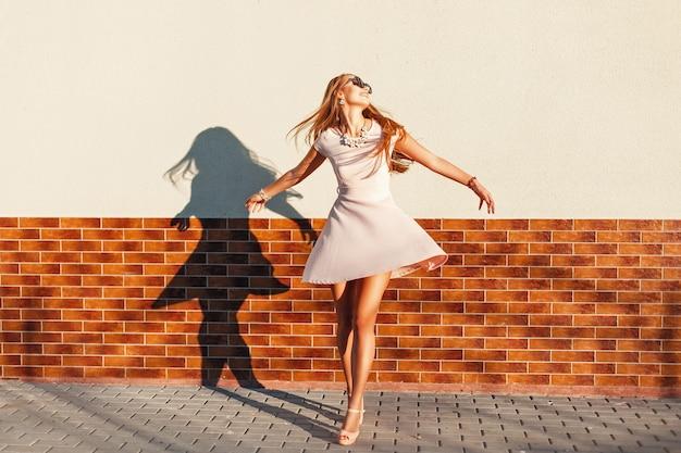 Красивая молодая жизнерадостная женщина с улыбкой в розовом платье крутится вокруг себя у стены